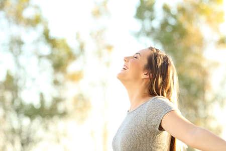 Zijaanzichtportret van een vrouw die verse lucht in openlucht in de zomer met bomen en hemel op de achtergrond ademen