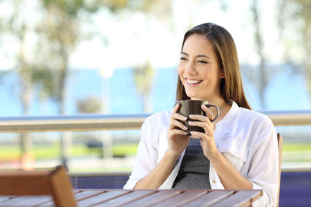 Happy relaxed woman holding a coffee mug in an apartment balcony with the beach and horizon in the background