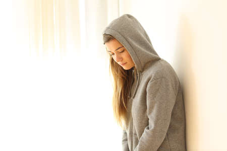 Portrait of a worried pensive teen looking down indoors with a white isolated background at side 免版税图像