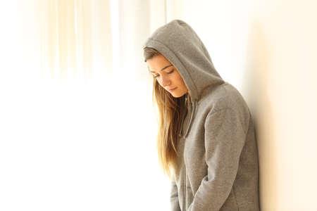 Portret van een bezorgde peinzende tiener die binnen met een wit geïsoleerde achtergrond aan kant kijkt