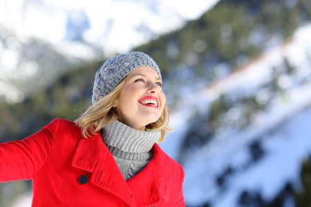 Portrét upřímné ženy sní na zasněžené hory v zimě