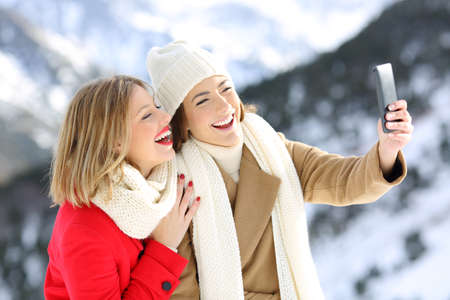 Two happy friends taking selfies in winter holidays with a snowy mountain in the background