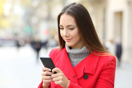 Serious woman using a smart phone standing on the street in winter