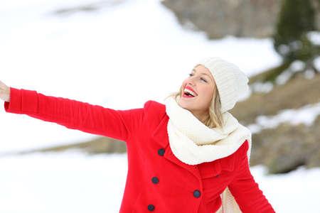 Portrét upřímné ženy v červené požívající venku v zasněžené hory v zimě