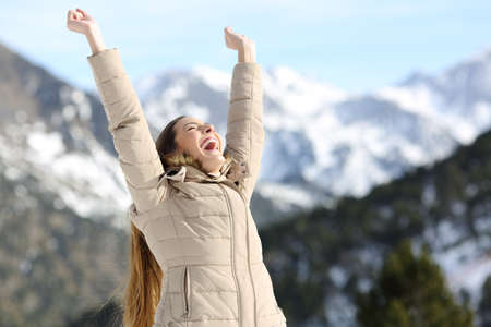 Excited woman raising arms celebrating success in the snowy mountain in winter Foto de archivo