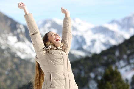 Mulher excitada, levantando os braços, comemorando o sucesso na montanha de neve no inverno Foto de archivo