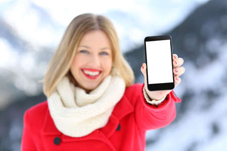 Front view portrait of a girl in red showing a blank smart phone screen in a snowy mountain in winter