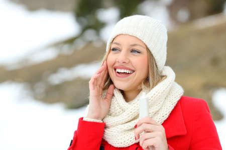Šťastná žena hydratační pokožku na obličej s hydratačním krémem v zimě v zasněžené horu Reklamní fotografie
