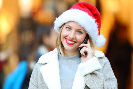 Front view portrait of a girl calling on mobile phone and looking at you in christmas holidays on the street with a storefront in the background Stock Photo