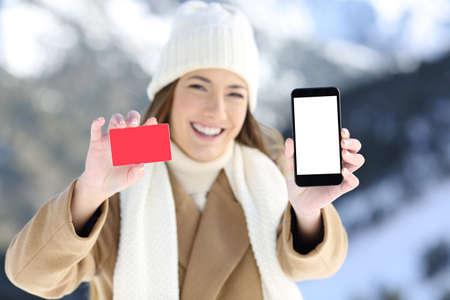Čelní pohled portrét ženy zobrazující karty a telefonní obrazovky v zasněžené hory v zimě