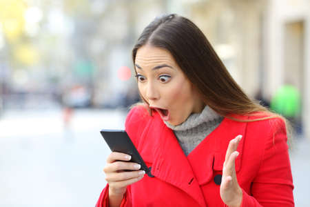 Amazed woman reading news on line in a phone on the street in winter