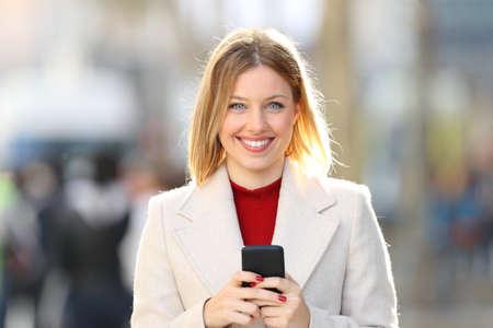 Čelní pohled portrét ženy nosí kabát představující pohledu na vás držení chytrý telefon na ulici v zimě
