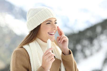 Dame die haar gezichtshuid hydrateert met vochtinbrengende crèmeroom in een sneeuwberg in de winter Stockfoto - 91250565