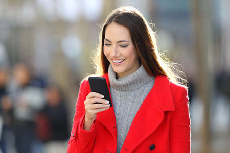 Happy woman wearing a red coat walking and using a smart phone on the street in winter Reklamní fotografie