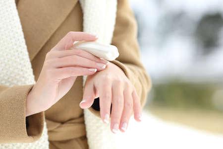 Zblízka ženy hydratační ruce s hydratačním krémem v zimě se zasněženou horou v pozadí Reklamní fotografie