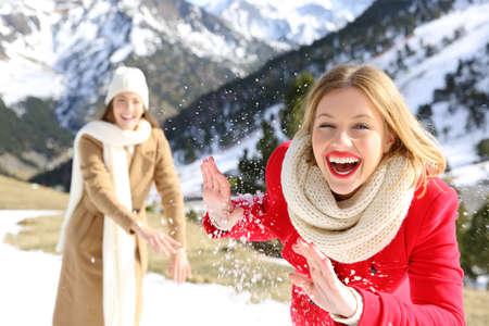 Dva přátelé vtipují házet sněhové koule na dovolené v zasněžené hory v zimě Reklamní fotografie