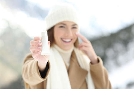 Front view portrait of a woman hydrating facial skin and showing product with a snowy mountain in the background in winter