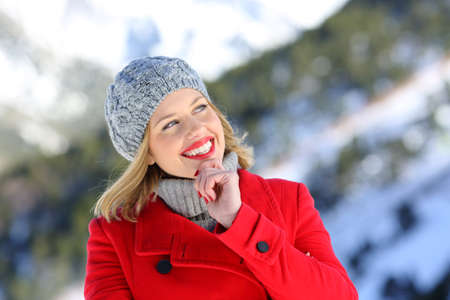 Portrait of a beautiful woman thinking in a snowy mountain in winter