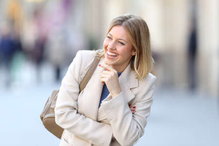 Portrait of a candid woman laughing alone on the street in winter Reklamní fotografie