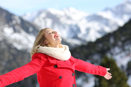Portrait of a carefree woman wearing a red coat breathing fresh air in the snowy mountain in winter