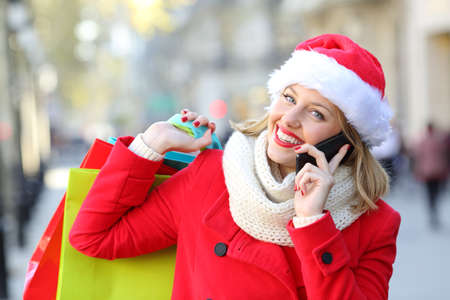 Front view portrait of a happy shopper wearing santa hat and red coat holding shopping bags and calling on phone on the street in christmas Stock Photo - 91250571