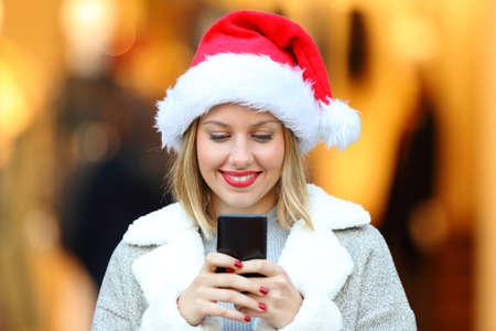 Čelní pohled portrét šťastné dívky posílání chytrý telefon zpráv v christmas svátky na ulici