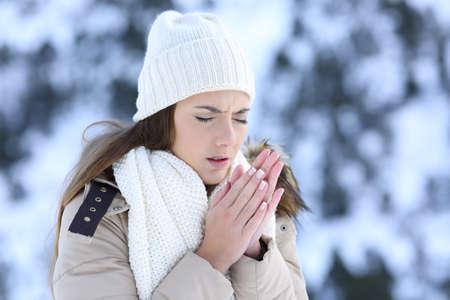 Žena trpí chladnou zimu venku se zasněženou horou v pozadí