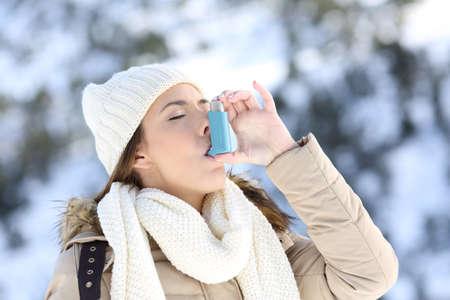 Portrét ženy pomocí astma inhalátor v chladné zimě s zasněžené hory v pozadí