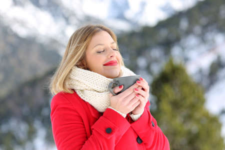 Portrait of a relaxed lady breathing fesh air and holding a coffee mug in a snowy mountain in winter Standard-Bild