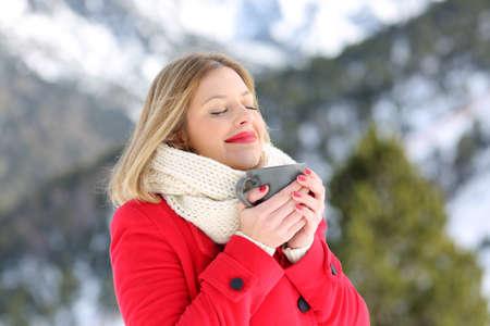 Retrato de una dama relajada respirando aire fesh y sosteniendo una taza de café en una montaña nevada en invierno Foto de archivo