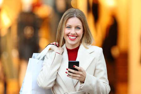 Front view portrét nakupující drží nákupní tašky a telefon na tebe na ulici obchodního domu Reklamní fotografie