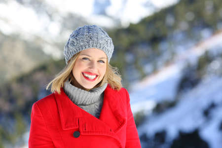 Portrait of a beautiful fashion woman smiling looking at you in a snowy mountain in winter