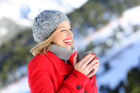 Portret van een gelukkige vrouw die het rode laag verwarmen met een kop van hete koffie in een sneeuwberg in de winter draagt Stockfoto
