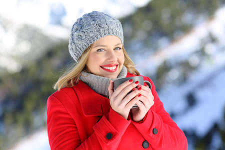 Portrait od a fashion happy woman wearing red coat posing holding a coffee mug in a snowy mountain in winter