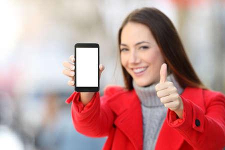 女性の冬の通り上に親指で空白のスマート フォンの画面を表示 写真素材
