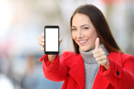 Woman showing a blank smart phone screen with thumbs up on the street in winter Foto de archivo