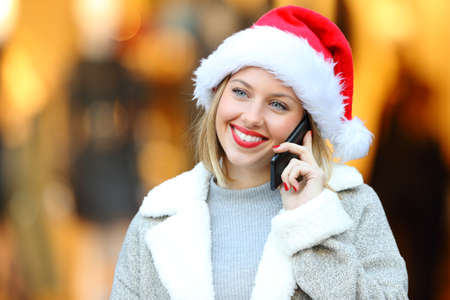 Front view portrait of a happy lady calling on mobile phone in christmas holidays on the street