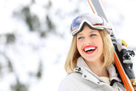 Portrét šťastný lyžař drží lyže pohledu na stranu s zasněžené hory v pozadí