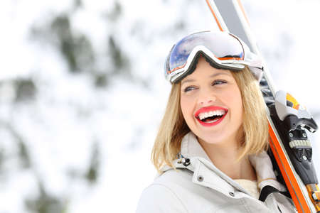 Portrait of a happy skier holding skis looking at side with a snowy mountain in the background