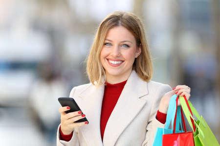 Čelní pohled portrét šťastný shopper drží nákupní tašky a chytrý telefon při pohledu na kameru na ulici v zimě