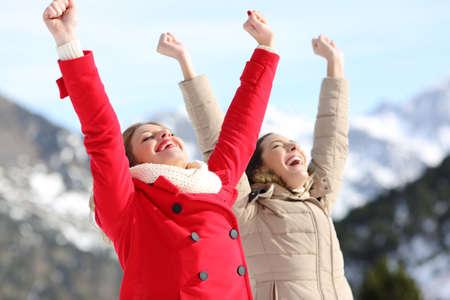 Dvě vzrušené ženy, které v zimě zvedají paže se zasněženou horou v pozadí Reklamní fotografie