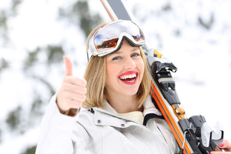 Portrait of a happy skier with thumbs up in a slope with a snowy mountain in the background