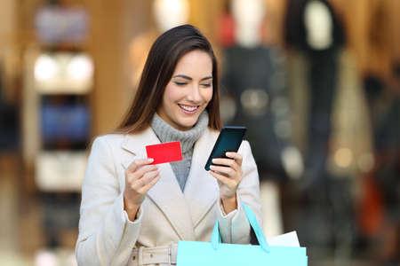 Šťastný zákazník drží nákupní tašky platí on-line s telefonem a kreditní kartou na ulici v zimě