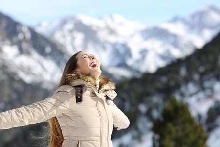Portrét vzrušené ženy smát v zimě s zasněžené hory v pozadí