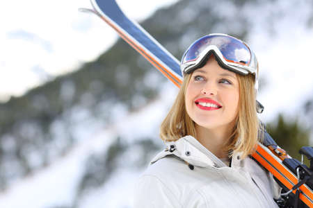 Portrait of a happy skier looking above with a snowy mountain in the background