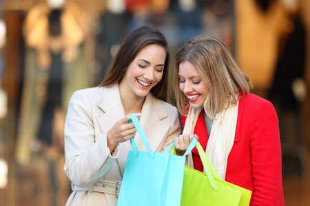 Dva šťastní zákazníci, kteří v zimě ukáží produkty v nákupních taškách na ulici