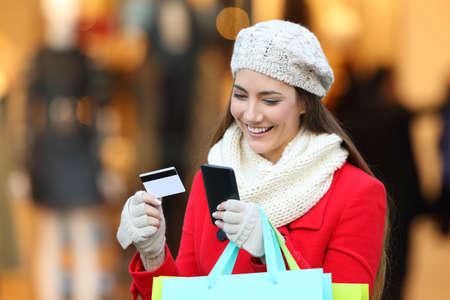 Šťastný zákazník platit on-line s telefonem a kreditní kartou na ulici v zimě s storeftont v pozadí Reklamní fotografie