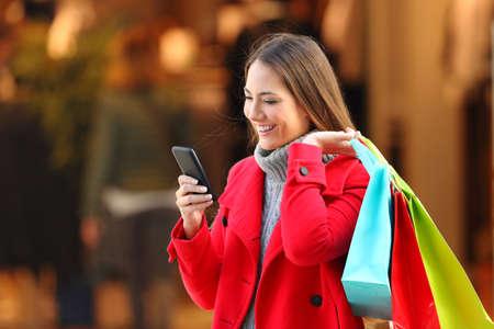 Šťastný zákazník s červeným pláštěm nakupuje a používá inteligentní phpone na ulici v zimě Reklamní fotografie