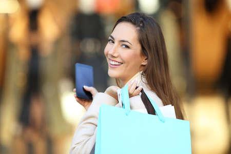 Pohled zezadu portrét šťastný zásobník drží chytrý telefon a nákupní tašky na vás na ulici v zimě Reklamní fotografie