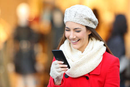 Portrait of a happy woman wearing red coat reading smart phone content in a commercial center in winter Reklamní fotografie